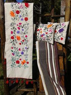 Pie de cama y almohadones bordados a mano