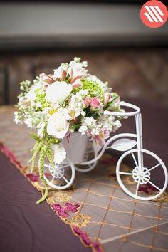 Centro de mesa de flores mixtas en tono pastel, con base en forma de bicicleta. Ideal para una boda romántica o en estilo vintage.