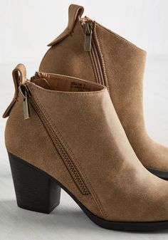 If your dearest footwear desires involve a versatile hue, a sturdy heel, and a sleek design, then - huzzah - wish granted! These taupe ankle boots tout textured faux leather, bold block heels, and posh pull-on tabs, and as a bonus, they also feature a pair of diagonal bronze zippers opposite functional zip closures for an edgy final touch.