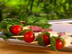 12 bamboo skewers  24 cherry tomatoes  24 basil leaves  12 ounces salami, cut into 1-inch cubes  12 ounces smoked mozzarella, cut into 1-inch cubes  Olive oil  Freshly cracked black pepper    #foodnetwork   #recipe
