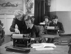 A teacher coaching her students on learning to type with an Imperial typing machine in 1944.