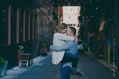 Man lifting his fiancé in an alley
