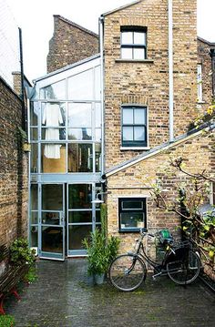 A two storey glazed and galvanised steel structure to the rear left of the property mixes with a more traditional brick third story extension to the right, providing additional living space and light