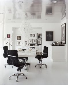 White walls, floors and furniture, black chairs, framed photos.  Miguel Flores-Vianna | 1stdibs Photo Archive Search