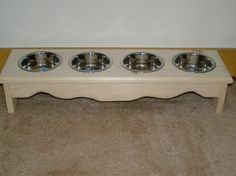 small dog/cat food bowl stand 4 bowl elevated feeder by cheeks63, $59.95.  I like this for our fur grandbabies.  One for the water & the other three for food.  It can be stained or painted as well as personalized upon request.