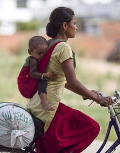 Babywearing mama and child in Nepalgunj, Nepal where bike travel is the usual transportation.