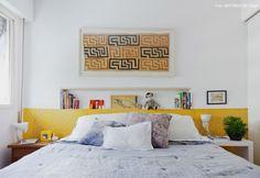 Quarto com nicho na parede, papel de parede amarelo e tecido africano emoldurado.