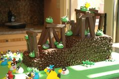 Interactive Angry Birds Cake!! - the birds, pigs, lettering, grass are all fondant, the cake iced in buttercream.  The slingshot was attached to the base & allowed all the kids to play angry birds & slingshot the pigs.