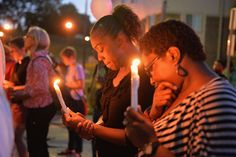 FILE - Mourning participants pause in a moment of prayer during a candlelight vigil held in honor of... - Michael B. Thomas/Getty Images