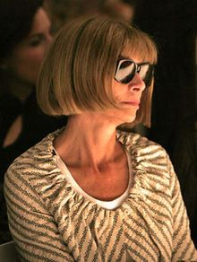 Anna Wintour wearing sunglasses and a grey-and-white striped top in a dark background looking to the right