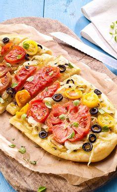 Focaccia mit Tomaten und Zwiebeln: Italienisches Brot mit Tomaten, Gemüsezwiebeln und Oliven