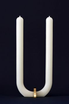Our U Candle is a hand poured, dual burning candle made of white beeswax. It is secured in place by a solid brass holder, which wraps atop the candle's lofted base. Candels, Taper Candles, White Candles, Chandeliers, Studio U, Unique Candles, Burning Candle, Candle Sconces, Candle Art