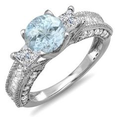 Celebrate your past present and future together with this classic diamond engagement or anniversary ring. Glimmering with the trio of center round Aquamarine and princess cut diamonds set in sleek 10 karat white gold this beautiful ring comes to a total carat weight of 3.15 carat. Additional round diamonds cascade down each side of the band. Chic and elegant this will make a ring that will never go out of style.