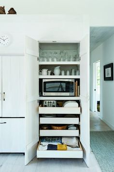 A concealed microwave and toaster on pull-out shelves in architect Sheila Narusaa's Cape Cod kitchen