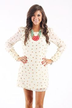 "The Mary Jane Dress, Ivory $41.00 This dress is beyond lovable! We love the sweet and simple design of the polka dots! This dress is fully lined and features a cuffed sleeve with five small buttons and a criss-cross design at the top of the back.   Fits true to size. Miranda is wearing a small.   From shoulder to hem:  Small- 31""  Medium- 32""  Large- 33"""