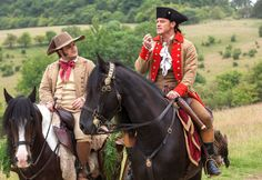 Gaston and Le Fou from Beauty and the Beast Movie Stills  Luke Evans (Gaston) and Josh Gad (Le Fou) ride horses in a green pasture.