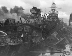 """Another view of the aftermath of the attack on destroyers USS Downes and USS Cassin, Pearl Harbour, 7 December, 1941. These ships, along with the 1914-vintage """"super-Dreadnaught"""" battleship, USS Pennsylvania, were in dry dock in the Navy Yard, across the strait from """"Battleship Row""""."""