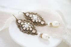 These beautiful earrings I created using highly detailed antique brass components that I set with Swarovski golden shadow crystal and Swarovski ivory / cream pearls and finished with matching pearls and Swarovski crystal rondelles. Earrings dangle 2-1/2 inches and are 1 inch at their widest. This is an original design by © Treasures by Agnes