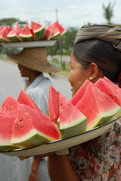 Two woman selling watermelon at a bus stop, Myanmar (Burma).  Photo: fergysnaps via Flickr