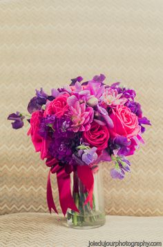 A bold bridal bouquet, using fuchsia dahlias, purple stock, hot pink roses, and purple sweet peas, tied together with a fuchsia satin ribbon.