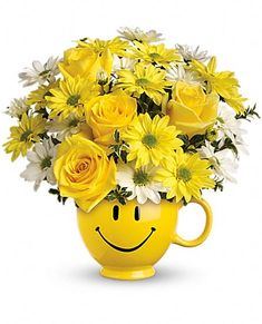 "Teleflora's Be Happy Bouquet with Roses in a reusable oversized coffee cup with ""Be Happy"" face."