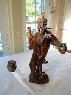 "Vintage Teak Wood Hand Carved Asian Oriental Old Man Fisherman Figurine.  He is all decked out carrying his shoulder pole and two carved water jugs, a couple of fish and his sun hat. The piece is not signed. This wonderful figurine measures 12"" high."