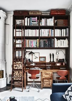 """What a gorgeous mix of """"stuff"""" - that stove, the old suitcases, the chairs. All conducive to inspire the occupant of this library/Study."""