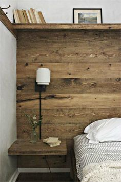 Rustic wood wall with shelf, hooks, built in bedside table.