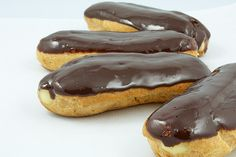 A photo of Chocolate Éclairs with Vanilla Bean Crème Pâtissière and Chocolate Ganache Glaze french pastries arranged in a semi circle.