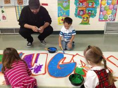 Mark Flores helps students in the Morton Grove Park District's preschool program paint a 16-foot mural for their classroom in the Austin Park Field House. | Photo courtesy of Laura Frisch
