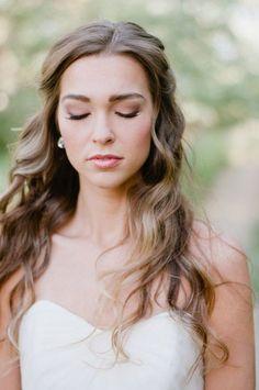 Novia con ondas sueltas y escote corazón que usan maquillaje de novia natural.