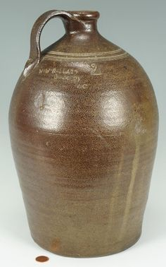 "North Carolina salt-glazed jug, stamped ""W. W. Ballard  Dockery, N.C."" (1852 - 1894). Pulled handle with concentric rings around the upper bulbous midsection and incised ""2"" denoting gallon capacity"