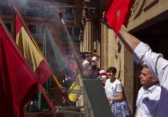 El veterano pamplonés Jesús Ilundain Zaragüeta (d), 'El Tuli', promotor del cántico a San Fermín previo al encierro en los años 50 y elegido por primera vez en una votación popular, durante el lanzamiento del chupinazo desde el balcón del Ayuntamiento de Pamplona.