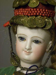 Il s'agit de la classique parisienne a corps tout articulé de chez Bru, issue du moule souriant en taille F. Elle mesure 40 cm et a la particularité de porter un vêtement traditionnel juif.