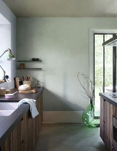 Green glass demi-john adds a hit of green to wood kitchen…