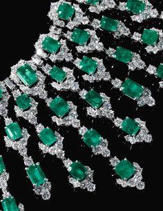Lot 579~ Impressive Emerald and Diamond Necklace BULGARI, Circa 1970 Estimate: 285,000 – 470,000 CHF Suspending a graduated fringe of step-cut Emeralds, highlighted with Brilliant-cut and Baguette Diamonds, signed Bulgari, Case stamped Bulgari.