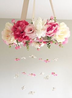 This is a listing for a flower mobile/floral chandelier in beautiful pink, peach, and white shades completed with beautiful greenery filling, satin ribbon wrapping the mobile base, and ribbon to hang the mobile with. Beautiful 18mm crystals hang elegantly and are strongly secured from 6 strands. This would be the perfect decor for a nursery or childs room, and it would also be beautiful used in a photoshoot or wedding. This is a LOVELY baby shower gift or birthday gift for that…