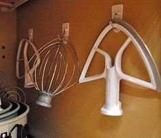 Hang mixer attachments inside cupboards.....on command hooks. Great idea!