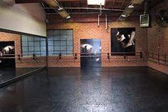 home dance studio with black floor and ballet barre