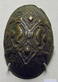 9th C. Norway. Copper alloy oval brooch; single piece construction; nine applied knobs; cast masks and Gripping Beast limbs in lattice-work grid; antique r...