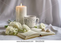 White objects on a white background. Burning candle, cup, notebook, cookies, ranunkulyus flowers.
