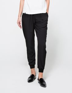 A lightweight, soft, pull on pant from Which We Want with minimalist style in black. Features an elasticized waistline, front pockets, relaxed fit, dropped crotch, tapered fit through the leg and ribbed cuffs.  • Lightweight pull on pants in black • E