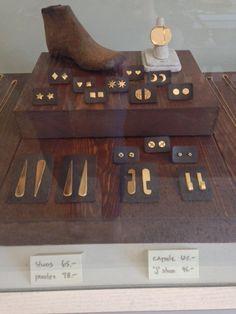 simple geometric brass/gold earrings on dark card and wood