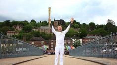 Torchbearer Lyndon Flavell holds the Olympic Flame on the Iron Bridge at Ironbridge Gorge on Day 12 of the Olympic Torch Relay