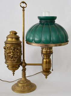 Brass Argon Oil Student Lamp with Repousse Cherubs - by Applebrook Auctions, adorned with a Green Glass Melon Shade.