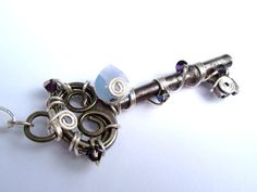 """Blue Opalite Swarovski Wire Wrapped Antique by FawneyFortune: This antique steel skeleton key is wire wrapped with silver wire and adorned with five iridescent, prismatic Swarovski crystals and a milky blue opalite Swarovski heart. Additionally, the top of the key is decorated with a hand shaped and hammered swirl to create a one of a kind bail. The pendant is hung from a silver-plated 18""""-21"""" adjustable chain with matching lobster clasp."""