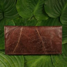 Unique, stylish and super light handmade purse, beautifully made from Teak  Leaves in the Lampang province, northern Thailand. Using environmentally  friendly materials and manufacturing processes, such as vegetable dyes and  sun drying, these products are 100% waterproof and completely leather free.  Each design is unique and has compartments for banknotes, coins, cards and  business cards.  Available in brown,black and beige size: 20 cm x 10.5 cm