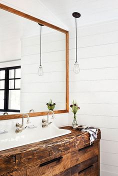 Beam vanity. Beam bathroom vanity. Bathroom features a reclaimed beam washstand fitted with a white trough and two gooseneck faucets tucked under a wood beveled mirror lining a shiplap wall. Reclaimed Beam vanity