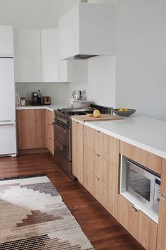 minimal kitchen, wooden lower cabinets, white uppers, neutral patterned rug