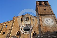 Photo made at the Cathedral Basilica of the Assumption of Lodi in Lombardy (Italy). In the image, illuminated by the morning sun and hat with blue sky, you see the facade of the church with the large rose window in the center and to his right side joined to it the big square bell tower with the clock by Roman numerals in the center .